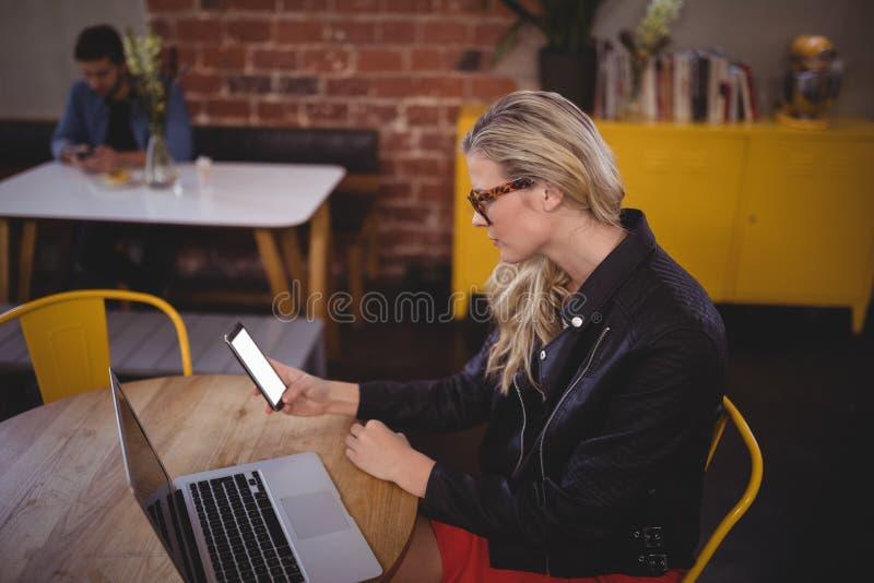 Ung kvinna som använder smartphonen, medan sitta med bärbara datorn på coffee shop arkivfoton