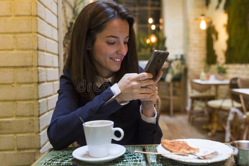 Ung kvinna som använder smartphonen på breakgast arkivfoton
