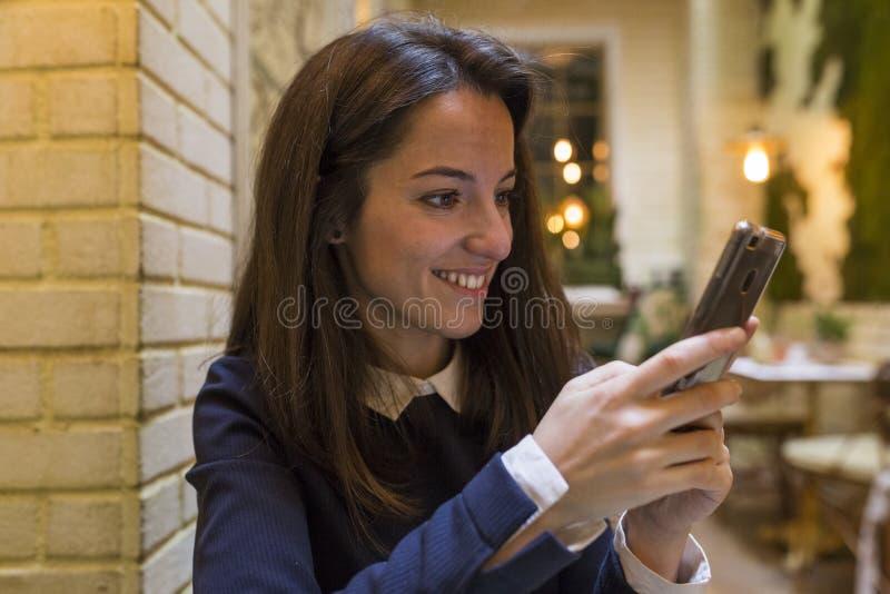 Ung kvinna som använder smartphonen på breakgast royaltyfri foto