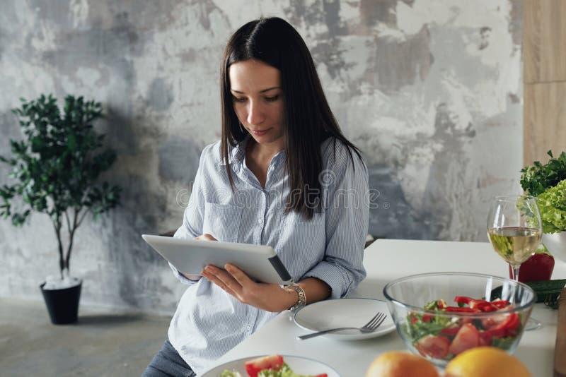Ung kvinna som använder Webinar för digitalt minnestavlahem frilans- arbete royaltyfri foto