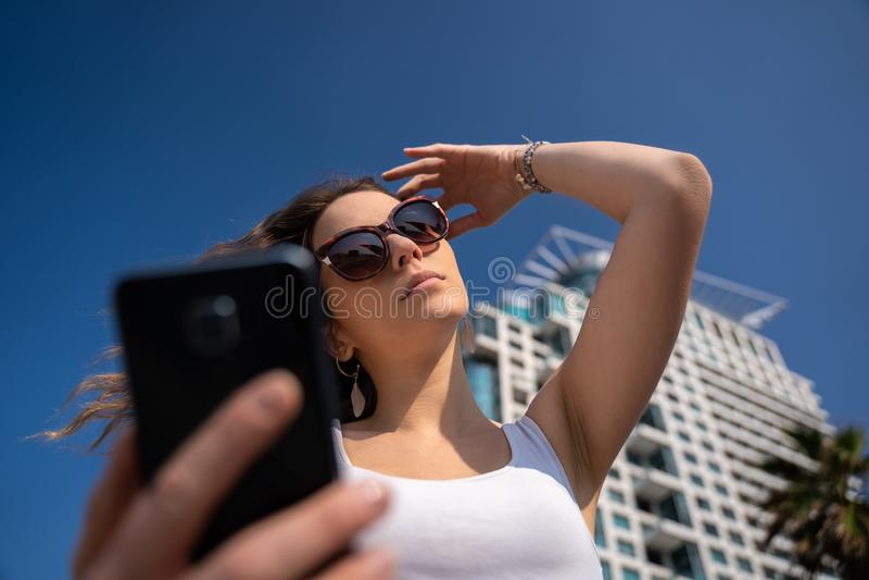 Ung kvinna som anv?nder telefonen Stadshorisont i bakgrund arkivbild