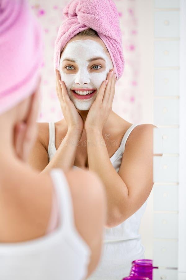 Ung kvinna som applicerar ansiktsbehandlingen som rentvår maskeringen royaltyfria bilder