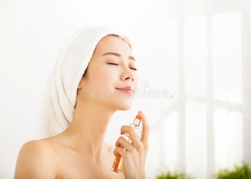 Ung kvinna som applicerar doft efter bad arkivfoto