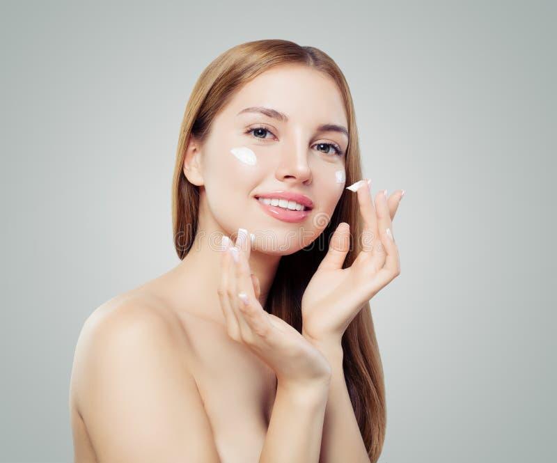 Ung kvinna som applicerar kräm på hennes klara hud härlig framsidakvinnlig Ansikts- behandling- och hudomsorgbegrepp royaltyfri fotografi