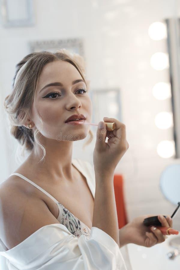 Ung kvinna som applicerar läppstift royaltyfri foto