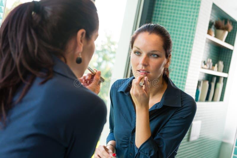 Ung kvinna som applicerar läppstiftsminkbadrummen arkivfoto