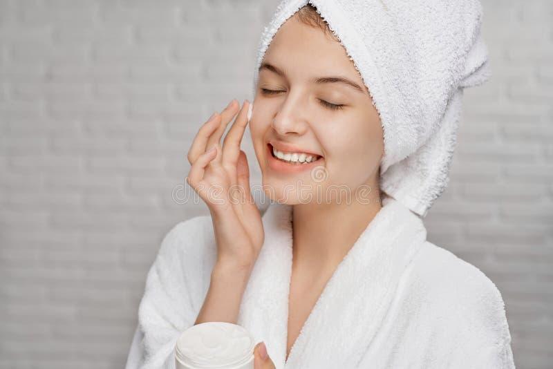 Ung kvinna som applicerar på framsidakräm för att hydratisera av hud arkivbilder
