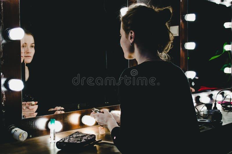 Ung kvinna som applicerar sminket som ser sig reflexion i spegel med kulor på dressingen i mörkt inre rum Flicka som applicerar c royaltyfria bilder