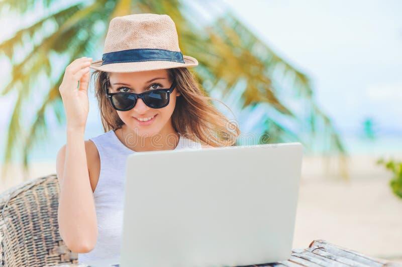 Ung kvinna som arbetar i bärbar dator på stranden Frilans- arbete arkivbild