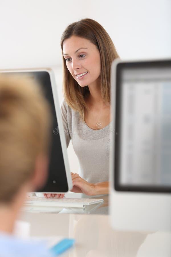 Ung kvinna som arbetar i datorrum royaltyfria foton