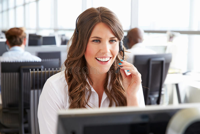 Ung kvinna som arbetar i en call center, hållande hörlurar med mikrofon arkivfoto