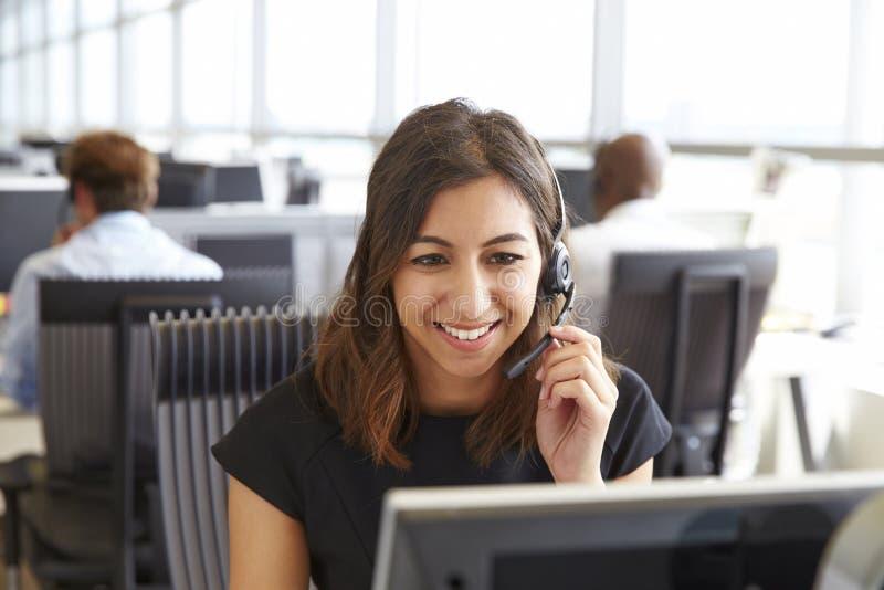 Ung kvinna som arbetar i en call center, hållande hörlurar med mikrofon royaltyfri fotografi
