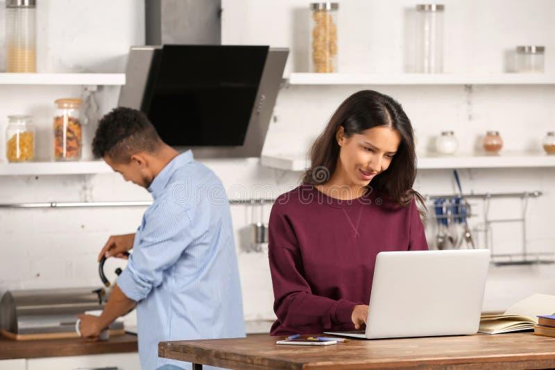 Ung kvinna som arbetar med bärbara datorn medan hennes pojkvän som lagar mat i kök arkivbild