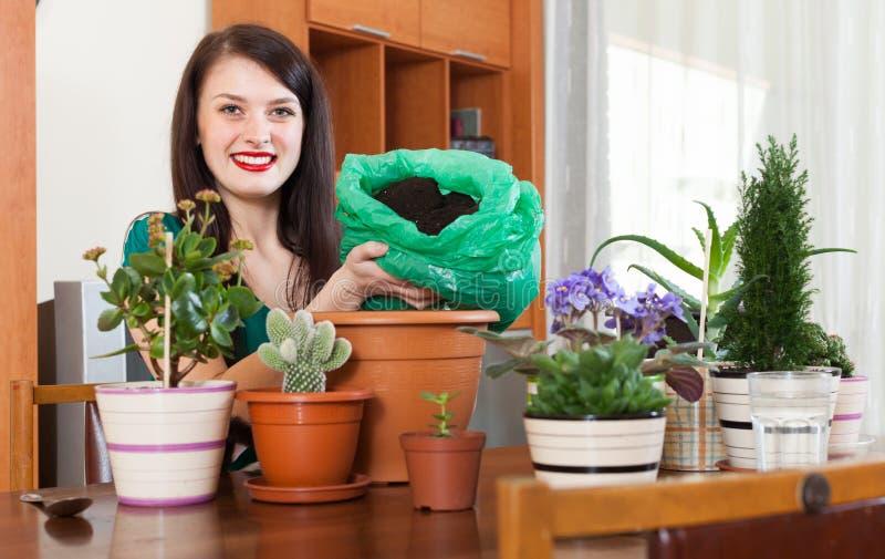 Ung kvinna som arbetar med blomman i krukor royaltyfri foto