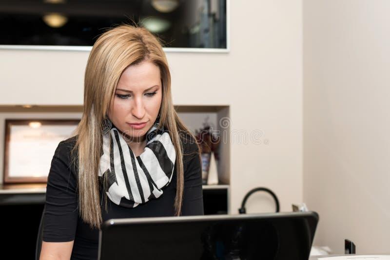 Ung kvinna som arbetar med en dator arkivfoton