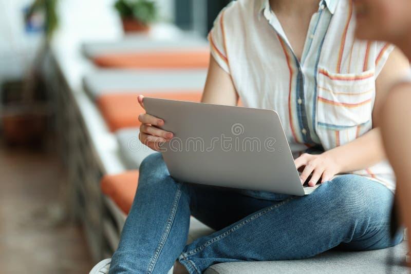 Ung kvinna som arbetar på bärbara datorn i arkiv arkivbild