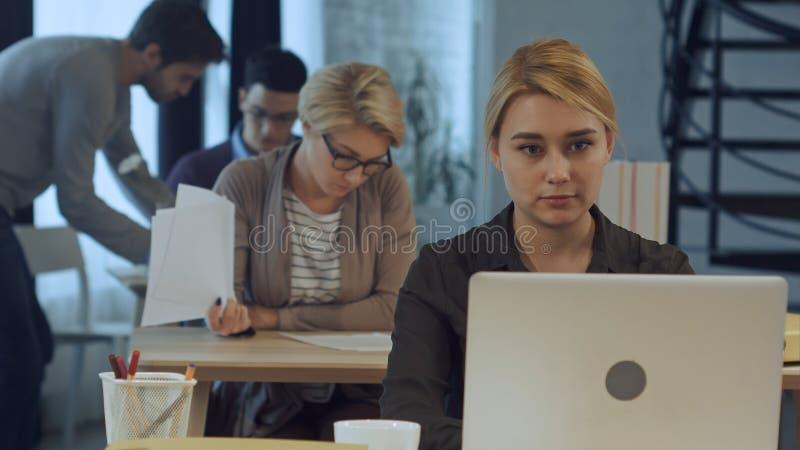 Ung kvinna som arbetar på bärbara datorn i det moderna kontoret royaltyfri foto