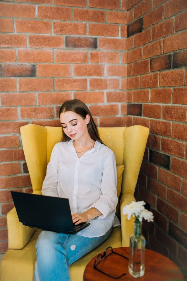 Ung kvinna som arbetar på bärbara datorn i en coffee shop arkivbild