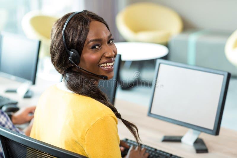 Ung kvinna som arbetar på datoren med hörlurar med mikrofon royaltyfria foton