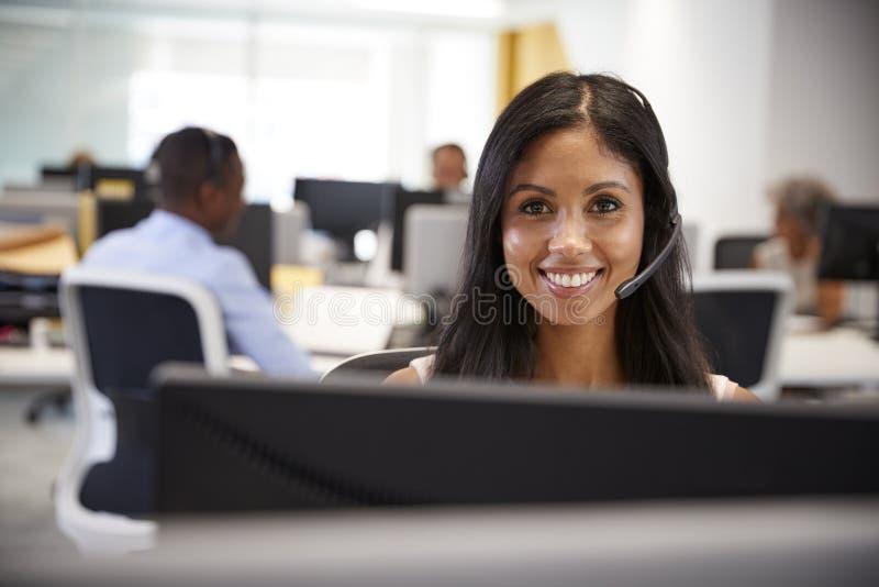 Ung kvinna som arbetar på datoren med hörlurar med mikrofon i upptaget kontor arkivbild