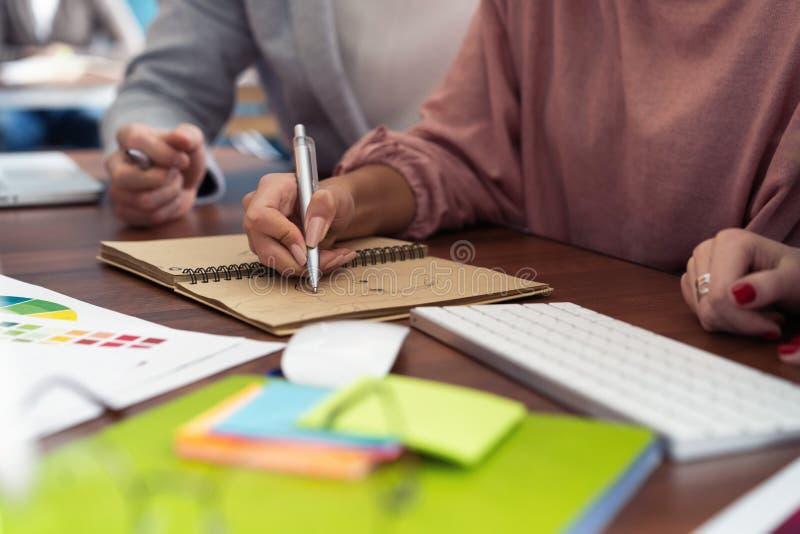 Ung kvinna som arbetar på hennes skrivbord som tar anmärkningar Fokus förestående som skriver på en notepad royaltyfria foton