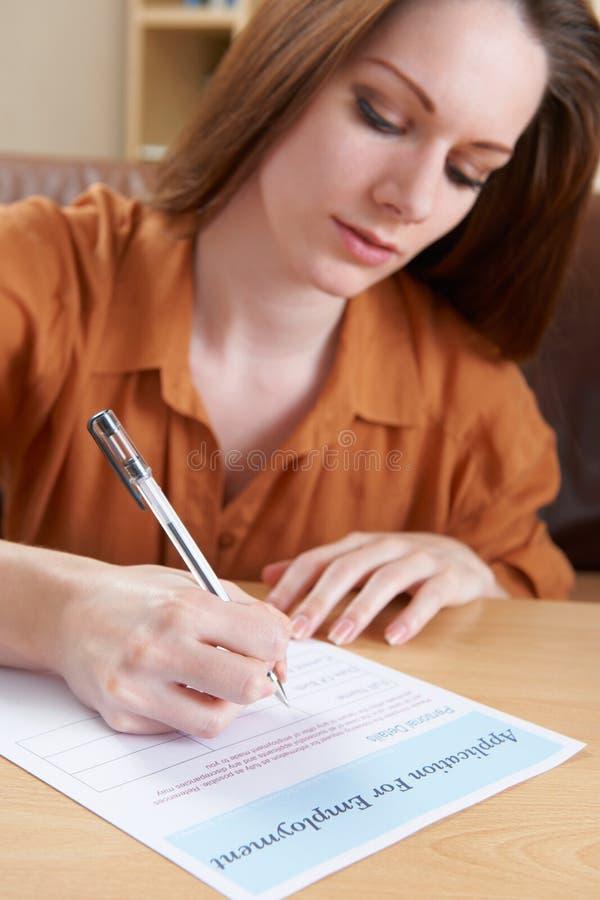 Ung kvinna som avslutar anställningansökningsblankett royaltyfria foton
