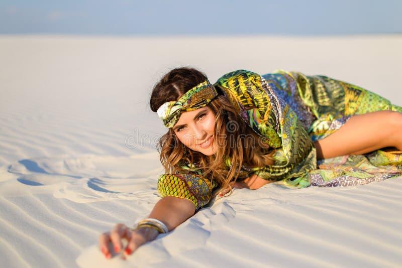 Ung kvinna som bär den gröna strandämbetsdräkten med liggande nolla för svart baddräkt arkivbild