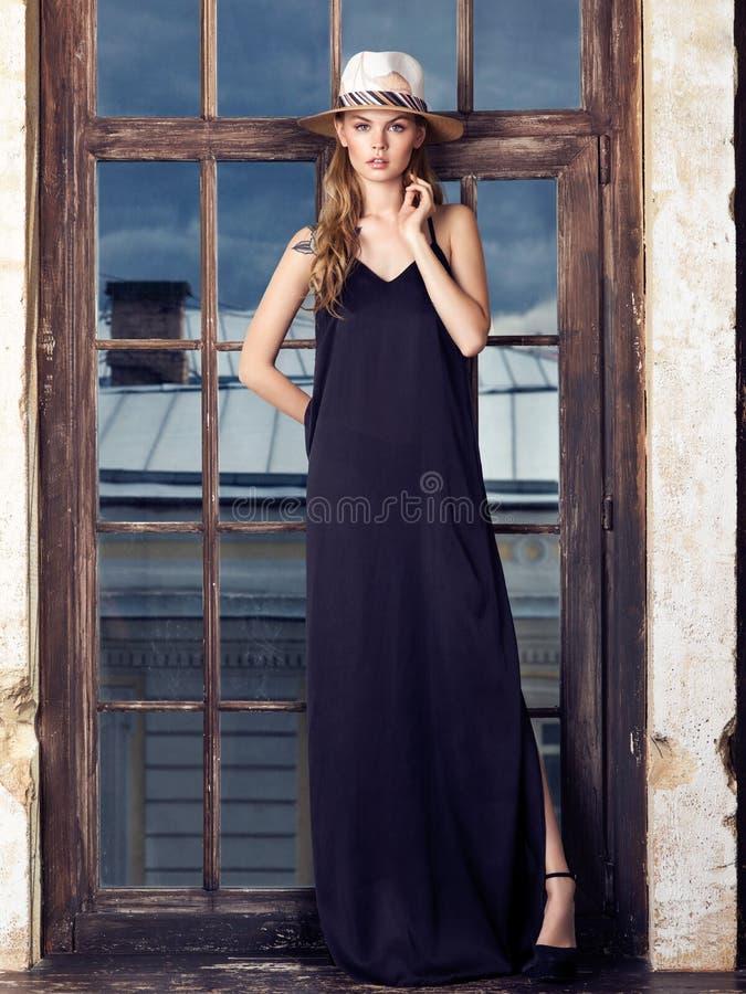 Ung kvinna som bär den långa svarta klänningen och hatten arkivfoto