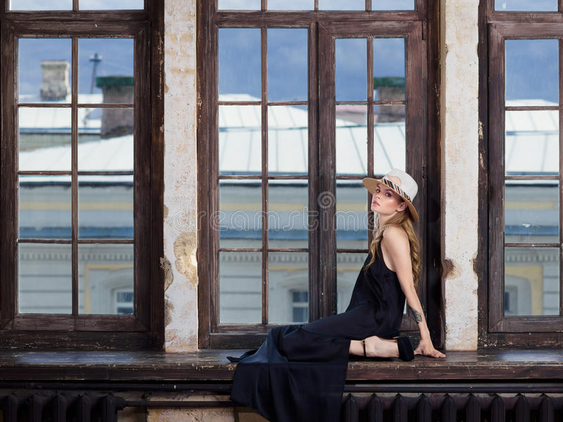 Ung kvinna som bär den långa svarta klänningen och hatten arkivbild