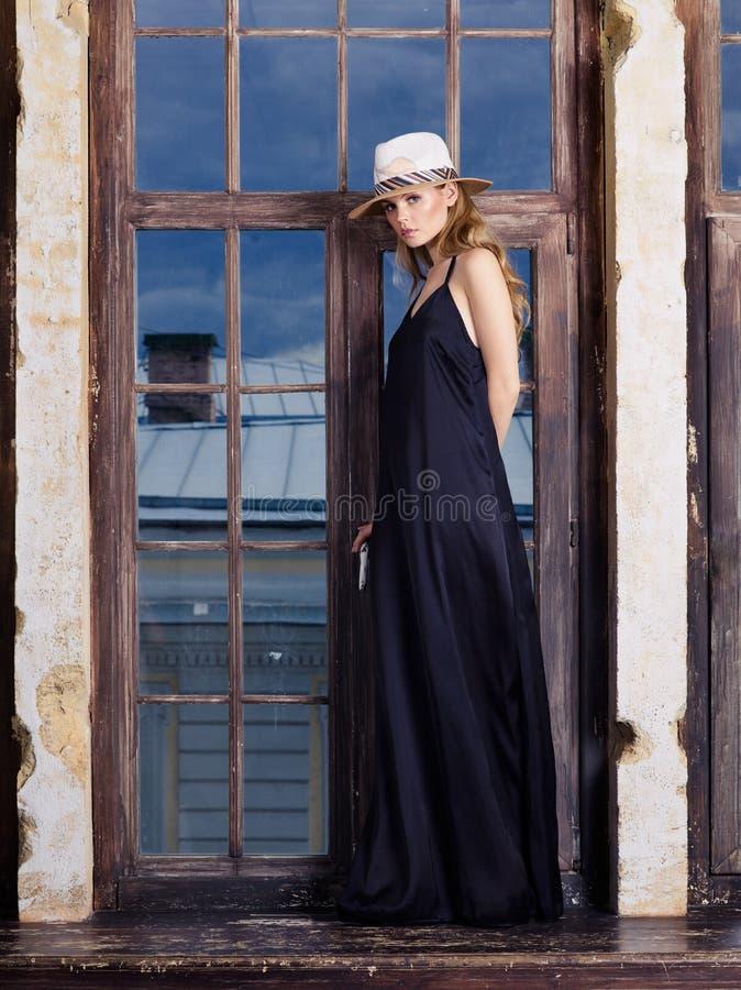 Ung kvinna som bär den långa svarta klänningen och hatten royaltyfri fotografi