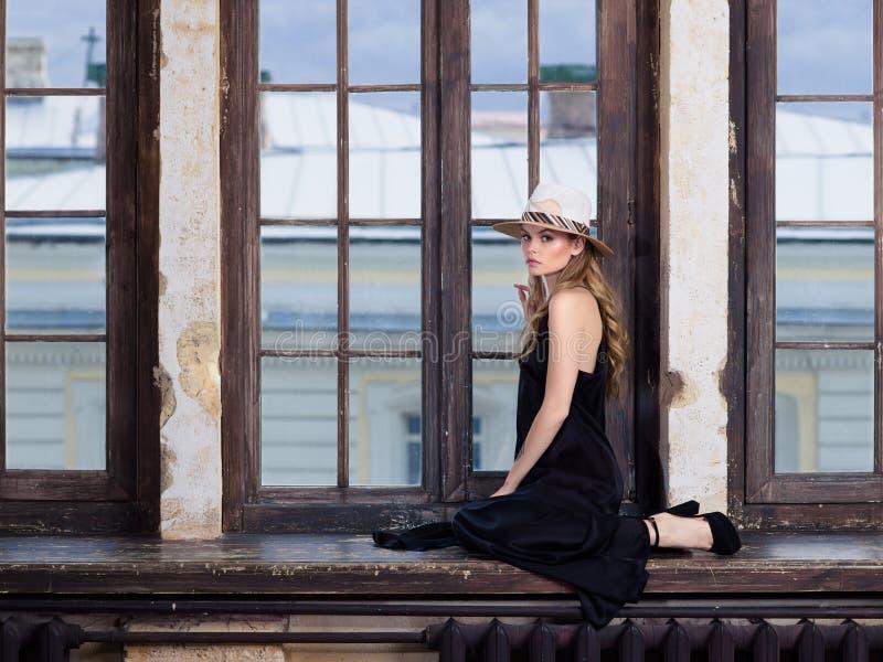 Ung kvinna som bär den långa svarta klänningen och hatten royaltyfri bild