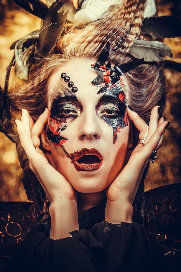Ung kvinna som bär den mörka dräkten Ljust smink- och rökhalloween tema arkivbild