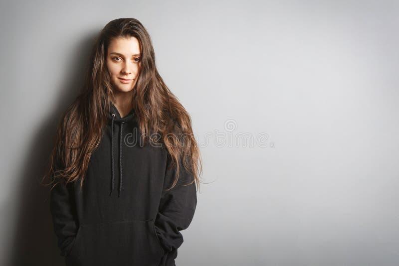Ung kvinna som bär den svarta tröjan som lutar mot den gråa väggen med kopieringsutrymme royaltyfria bilder