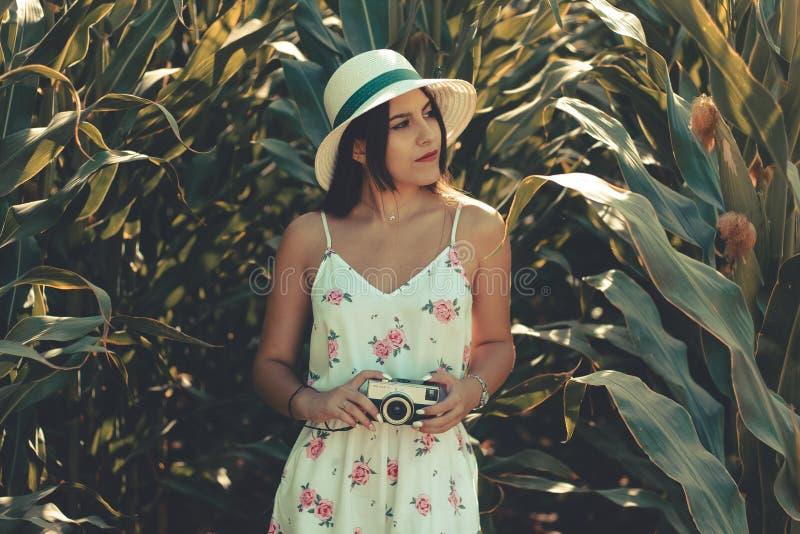 Ung kvinna som bär en blommig vit klänning som tar foto med den retro fotokameran arkivbilder
