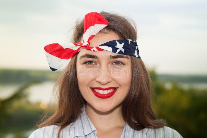 Ung kvinna som bär en head bandana med amerikanska flaggandesign arkivbild