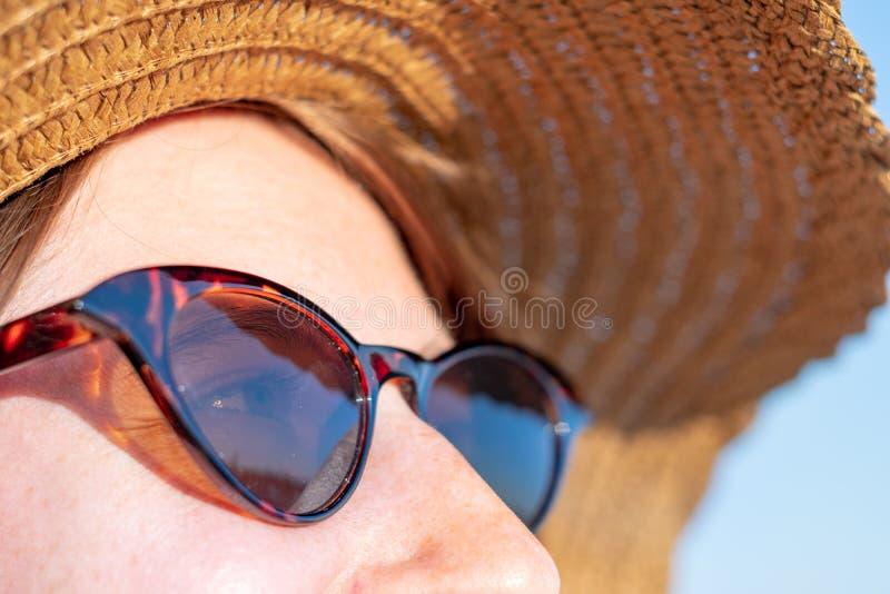 Ung kvinna som bär en sommarhatt och solglasögon, närbildstående fotografering för bildbyråer
