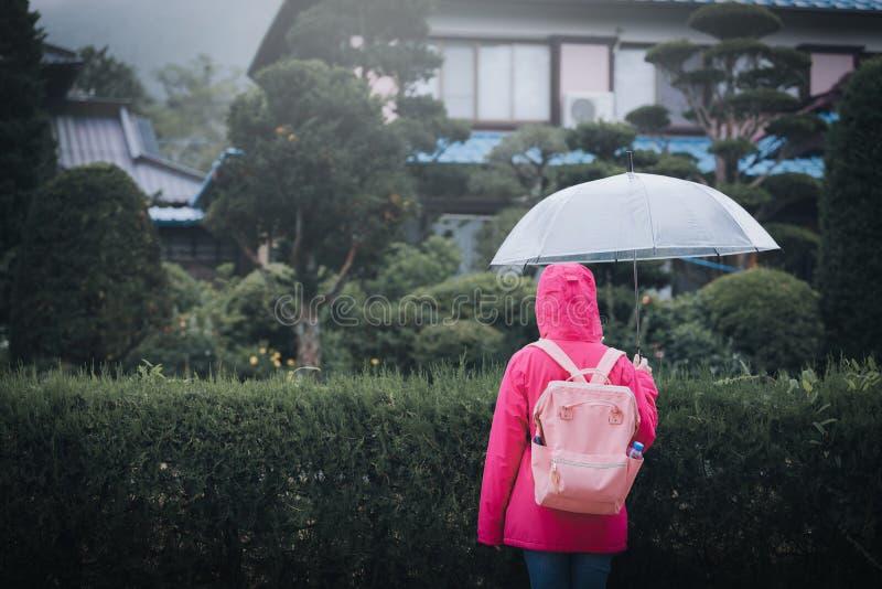 Ung kvinna som bär ett rosa omslag och innehav ett paraply på royaltyfri bild