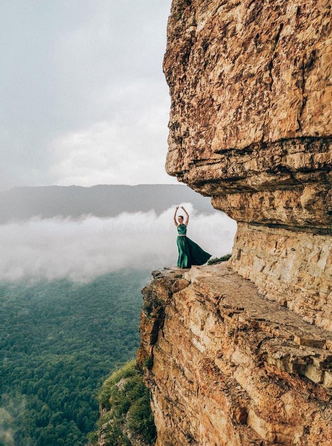 Ung kvinna som bär klänningen för lång gräsplan i berg Mezmay fotografering för bildbyråer