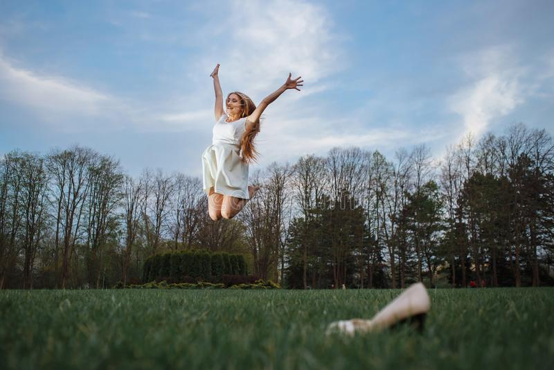 Ung kvinna som barfota hoppar på grön äng Frihet och hälsa i megapolicebegrepp royaltyfri foto
