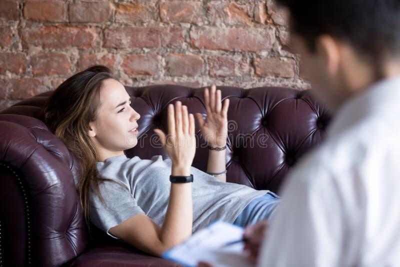Ung kvinna som berättar en psykologlägerledare om hennes problem royaltyfri fotografi