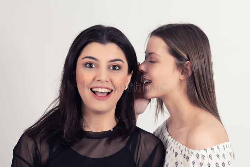 Ung kvinna som berättar hennes flickvän någon hemlighet skvallra två kvinnor royaltyfri foto