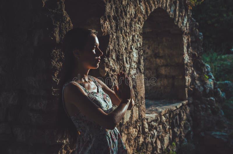 Ung kvinna som ber i den gamla fästningen för Stari stång, Montenegro Flickakontur på solnedgång Religion som mediterar, andlighe arkivfoto