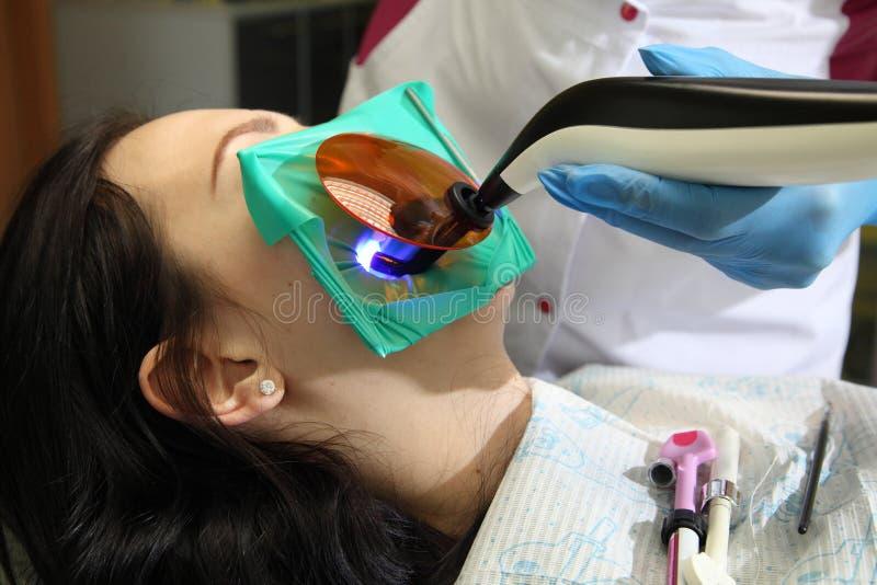 Ung kvinna som besöker tandläkaren på kliniken Manlig tandläkare med patienten i klinik royaltyfri fotografi