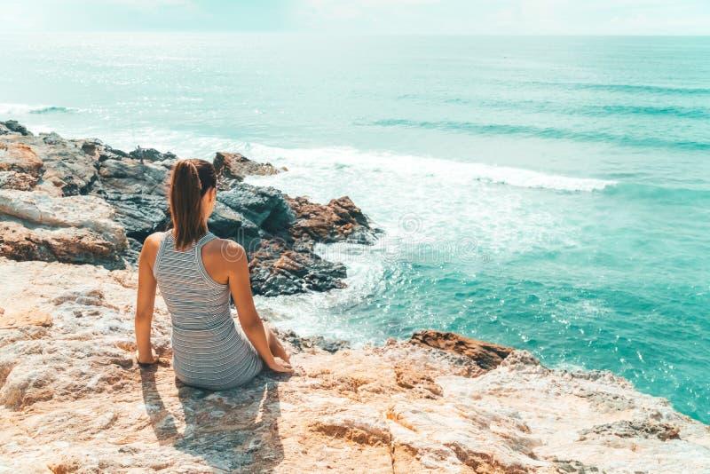 Ung kvinna som beundrar härligt landskap av klippor och havet i Portugal arkivfoto