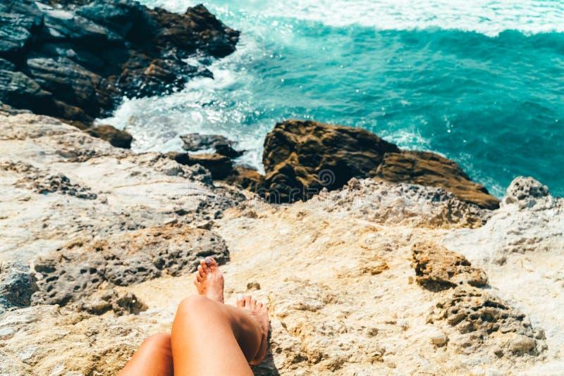 Ung kvinna som beundrar härligt landskap av klippor och havet i Portugal arkivbilder