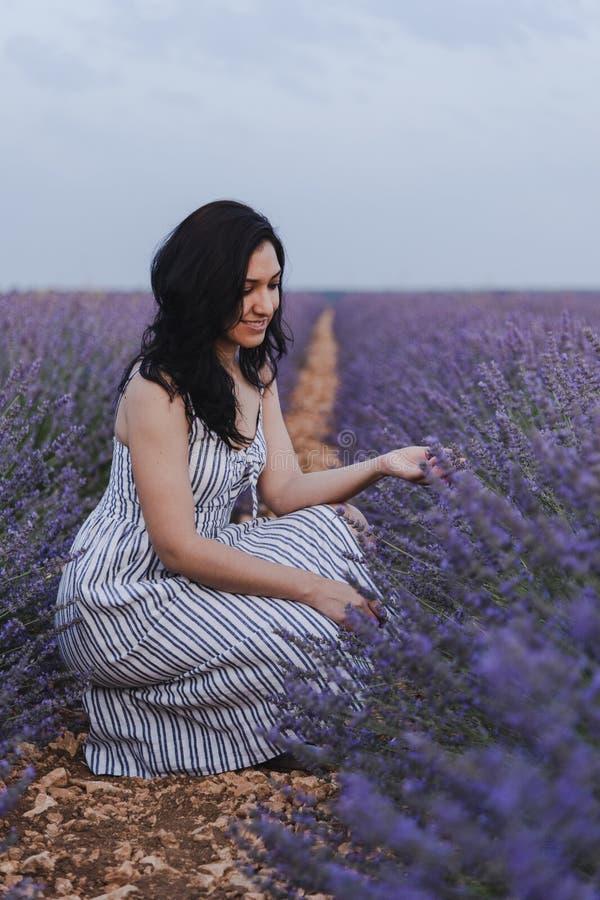 Ung kvinna som beundrar lavendel arkivfoto