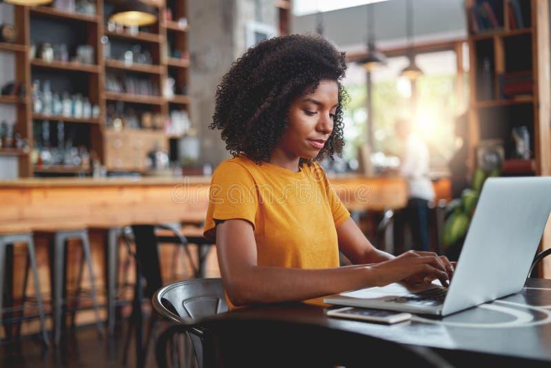 Ung kvinna som binder på bärbara datorn i kafé royaltyfria bilder
