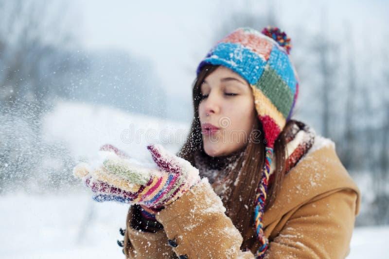 Ung kvinna som blåser snow till bort royaltyfri bild