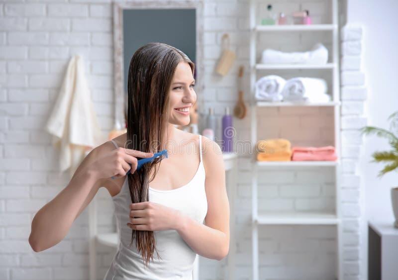 Ung kvinna som borstar hår, når att ha applicerat maskeringen arkivfoton