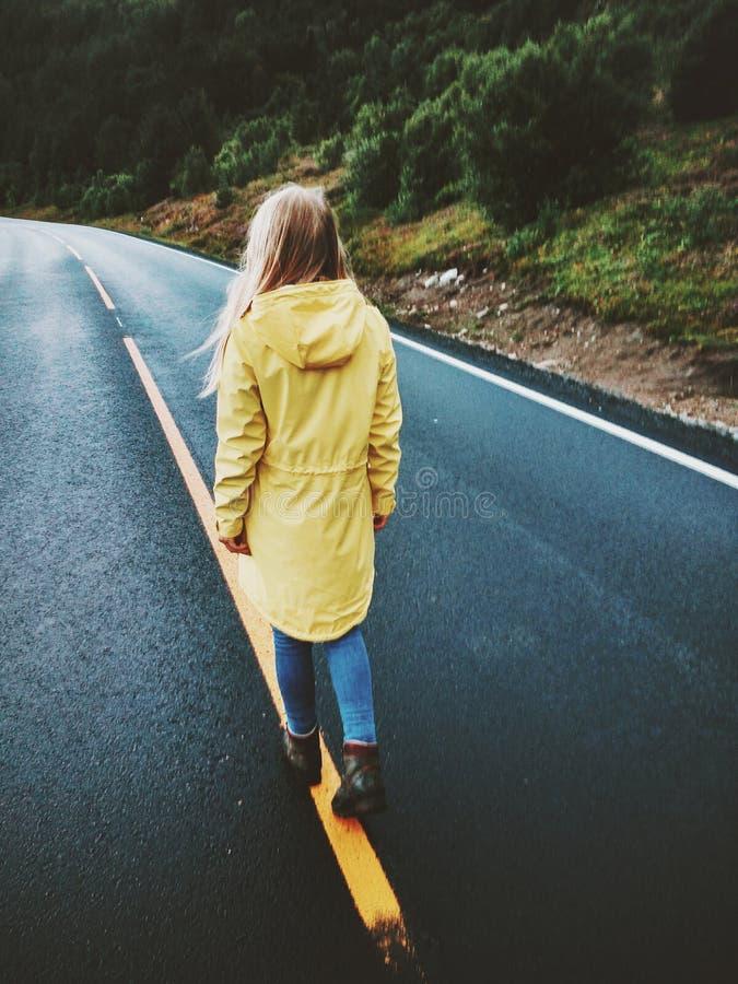Ung kvinna som bort går på vägen royaltyfri foto